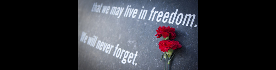 ARLINGTON, VA - SEPT 13, 2014: Red carnations laying against the granite wall of the Memorial Gateway entrance to the Pentagon Memorial dedicated to the victims of the September 11, 2001 attack.