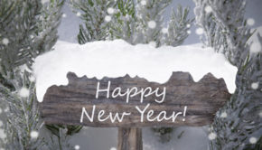 Wooden Christmas Sign With Snow And Fir Tree Branch In The Snowy Forest. English Text Happy New Year For Seasons Greetings Or Happy New Year Greetings. Christmas Atmosphere With Snowflakes